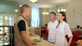 Couple talks with bartender in cozy confectionery shop. Lovely couple talks with smiling bartender standing at counter in cozy decorated confectionery shop stock video