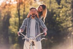 Couple with a tandem bicycle. Beautiful young couple is having fun while riding a tandem bicycle in the park. Girl is covering her boyfriend`s eyes Royalty Free Stock Photo