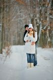 Couple with tangerines in winter forest Stock Photo