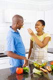 Couple tasting food in kitchen royalty free stock photography