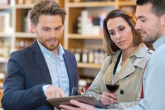 Couple tasting glass wine and checking tablet Royalty Free Stock Image