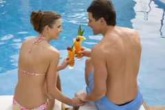 Couple tasting tropical drinks at poolside Royalty Free Stock Photo