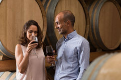 Couple tasting wine. Mature couple tasting a glass of red wine in a traditional cellar surrounded by wooden barrels. Happy mature women smelling a glass of red royalty free stock photography