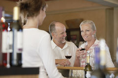 Couple Tasting Wine With Merchant In Foreground Royalty Free Stock Images