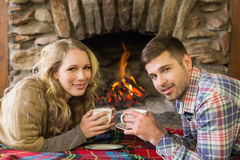 Couple with tea cups in front of lit fireplace Stock Photos