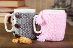 Couple of tea cups with knitted covers and biscuits. Books, wooden table Stock Images