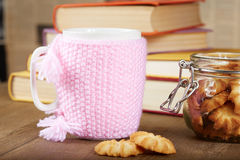 Tea cup with knitted cover and biscuits Royalty Free Stock Photo