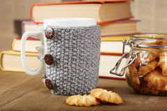 Tea cup with knitted cover and biscuits Stock Photography