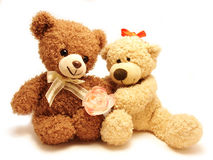 Couple of teddy-bears & rose. Couple of teddy-bears sitting together holding the rose Royalty Free Stock Image