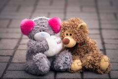 Couple of teddy bears sitting together on the street Stock Photo