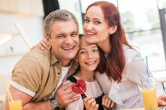 Couple and teen daughter in cafe. Mature couple and teen daughter with heart shaped lollipop in cafe stock photo
