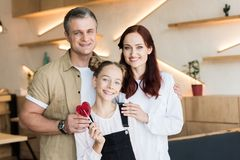 Couple and teen daughter in cafe. Mature couple and teen daughter with lollipop in cafe stock images