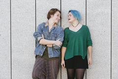 Couple of teen gay women isolated on a grey wall royalty free stock image