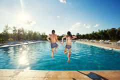 Couple teen jumping into pool Stock Photography