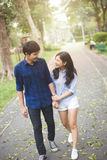 Couple teen. Couple walking in garden. Them hand in hand and smile with happiness stock image