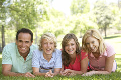 Couple And Teenage Children Lying On Grass Royalty Free Stock Photos