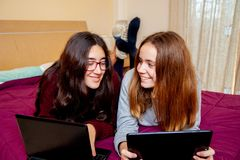 A couple of teenage girls hang out with their electronic devices, tablets and laptops in a bed royalty free stock images