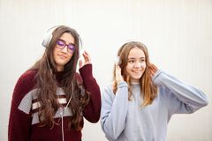 A couple of teenage girls have fun with their headphones royalty free stock image