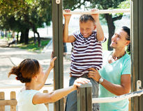 Couple with teenage son training on pull-up bar Royalty Free Stock Photos