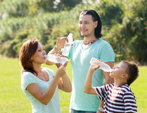Couple with teenager drinking water from  bottles Royalty Free Stock Photos