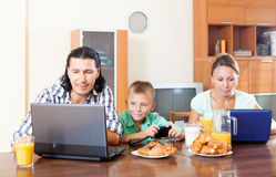 Couple with teenager having breakfast with electronic device. Happy adult couple with teenager having breakfast with electronic devices in morning at home Royalty Free Stock Image