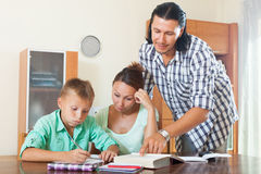Couple with teenager schoolboy doing homework Royalty Free Stock Photography