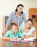 Couple with teenager son doing homework Stock Images
