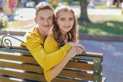 Couple teenagers on a bench stock images