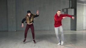 Couple of teenagers dancing indoor. Energetic boy and girl performing contemporary dance in studio. Concept of street dance stock footage