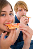 Couple of teenagers eating pizza. Isolated on white background Stock Images