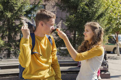 Couple teenagers feeding pigeons on city street Royalty Free Stock Images