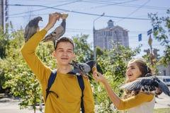 Couple teenagers feeding pigeons on city street royalty free stock image