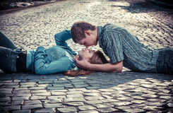 Couple of teenagers lying in street together Stock Images