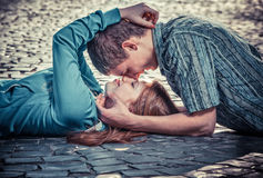 Couple of teenagers lying in street together Stock Photos