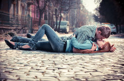 Couple of teenagers lying in street together Royalty Free Stock Photo