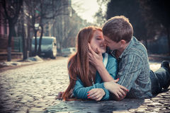 Couple of teenagers lying in street together Stock Image