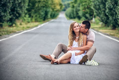 Couple of teenagers sit in street together Royalty Free Stock Photography