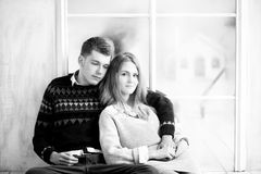 Couple of teenagers sitting against mirror wall. Black and white Royalty Free Stock Photos