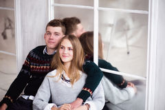 Couple of teenagers sitting against mirror wall Stock Photos