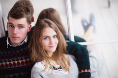 Couple of teenagers sitting against mirror wall. Photo of Couple of teenagers sitting against mirror wall stock image