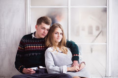 Couple of teenagers sitting against mirror wall. Photo of Couple of teenagers sitting against mirror wall stock photo