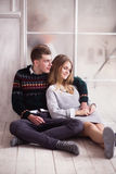 Couple of teenagers sitting against mirror wall. Photo of Couple of teenagers sitting against mirror wall stock photos