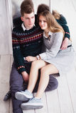 Couple of teenagers sitting against mirror wall. Photo of Couple of teenagers sitting against mirror wall royalty free stock photo