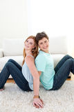 A couple of teenagers sitting on the floor Royalty Free Stock Photos