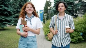Couple of teenagers walking outdoors talking holding books drinking coffee. Couple of teenagers girl and guy are walking outdoors talking holding books drinking stock video