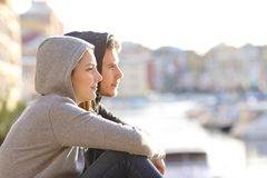 Couple of teens contemplating horizon in a coast town. Side view portrait of a couple of serious teens contemplating horizon in a coast town stock photo