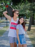 A beautiful girl with long chestnut hair dating with an attractive fellow in a park on a natural blurred background. Stock Images