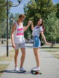 A laughing fellow teaching a beautiful girl riding on a longboard in a park on a natural blurred background. Stock Photos