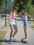 A laughing fellow teaching a beautiful girl riding on a longboard in a park on a natural blurred background. royalty free stock images