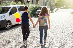Teens holding hands rear view. Friendship, first love. Couple teens holding hands rear view. Friendship, first love Stock Photos